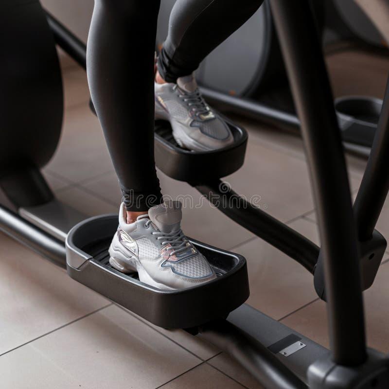 绑腿的年轻女人在体育运动鞋做在一台步进模拟器的心脏训练在健身房 女孩烧伤卡路里 免版税库存图片