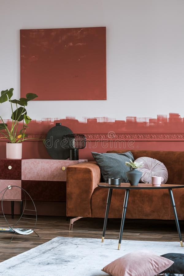 绒面革伯根地和与黑花瓶的粉红彩笔洗脸台有在优等的客厅内部的绿色叶子的 库存照片