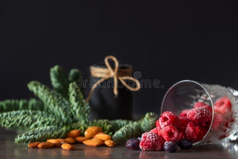 结冰的莓和蓝莓莓果落在桌上的一块玻璃外面 库存照片