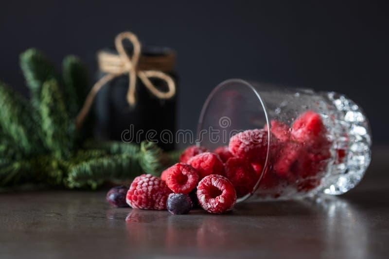 结冰的莓和蓝莓莓果落在桌上的一块玻璃外面 免版税库存照片