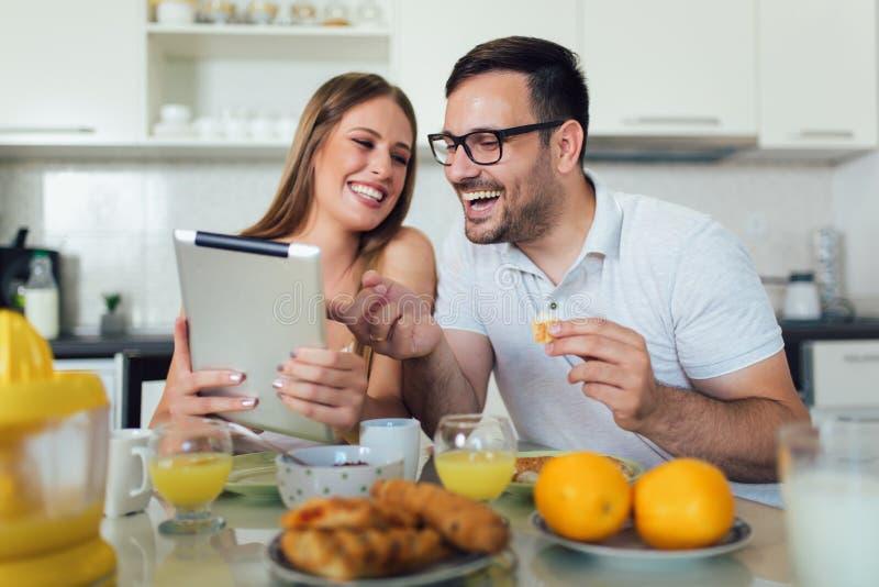 结合一起享受早餐时间在家和使用数字片剂 免版税库存照片