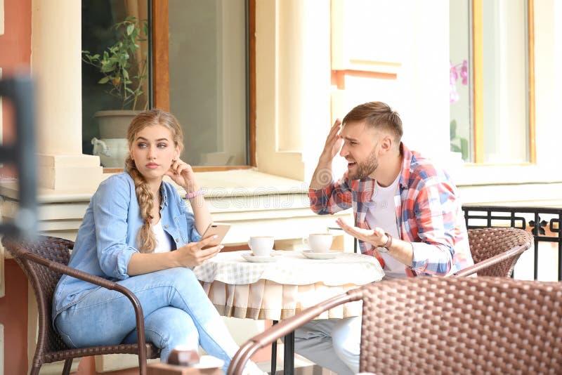 结合争论,当坐在咖啡馆,户外时 在关系的问题 图库摄影