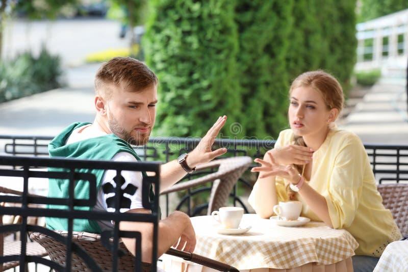 结合争论,当坐在咖啡馆,户外时 在关系的问题 免版税库存照片