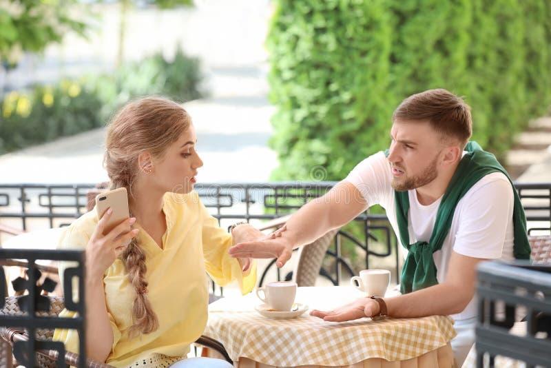 结合争论,当坐在咖啡馆,户外时 在关系的问题 免版税图库摄影