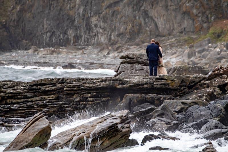 结合享受他们的婚礼在Elgol海滩在与红色Cuillin山的港na Cullaidh在海湾Scavaig的云彩下 图库摄影