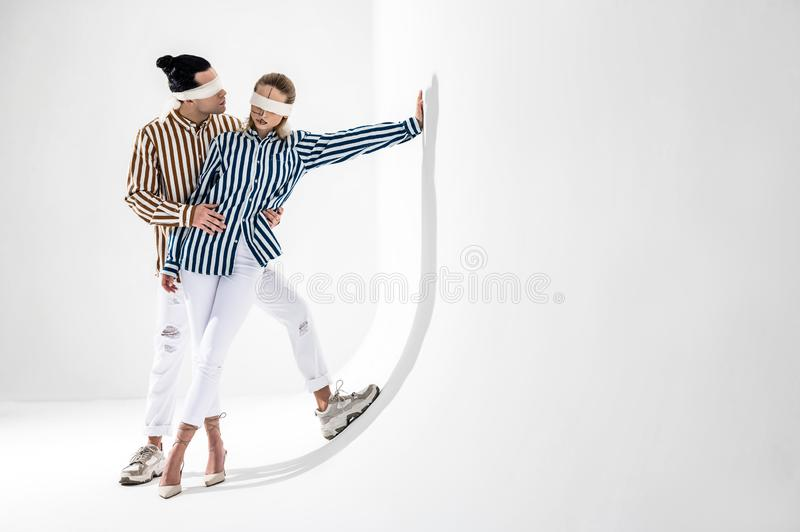 结合佩带的白色的长裤和一起摆在的镶边衬衣 免版税库存照片