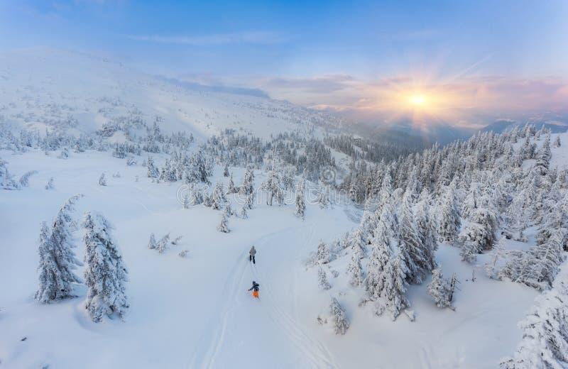 结合在一条修饰的弯曲的双重滑雪轨道的滑雪与山 图库摄影