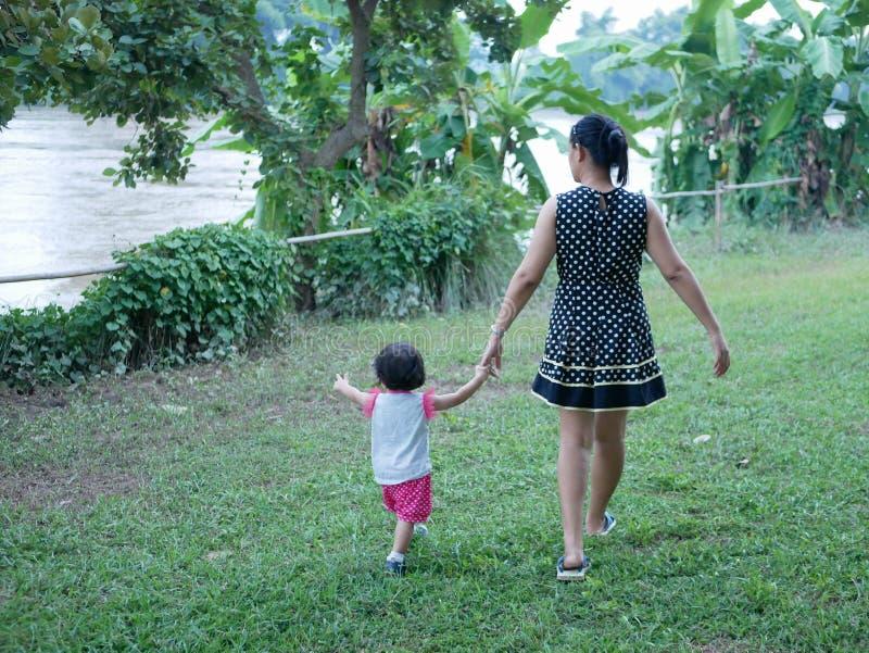 结合在一起使她的小女儿的手的亚裔母亲和有步行在一个室外绿草领域由河沿 库存图片
