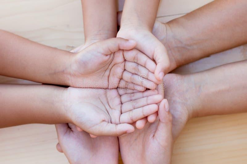 结合在一起使手的父母和孩子在木背景 免版税库存图片