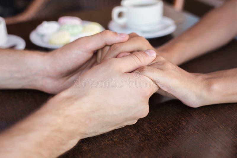 结合在一起使手的男人和妇女在咖啡馆 库存图片