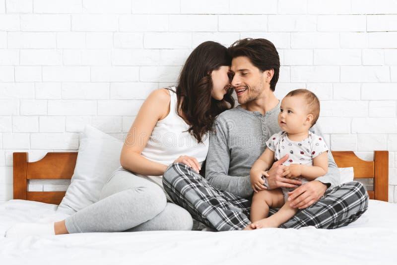 结合在与一点小儿子的床上的年轻千福年的夫妇 图库摄影