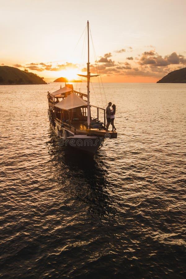 结合在享受在游艇板的爱日落 图库摄影