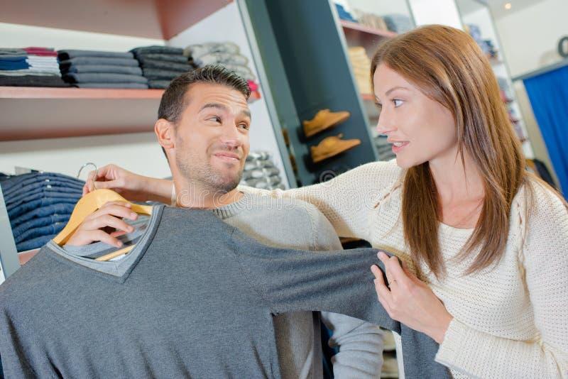 结合在拿着套头衫的服装店夫人反对人 免版税库存图片