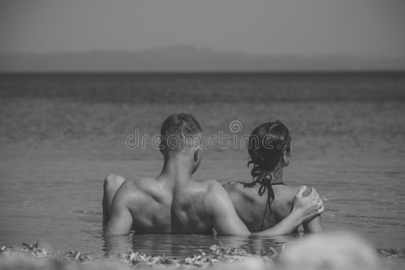 结合在放松在度假,蜜月的爱 放松愉快的夫妇,晒黑在海滩的太阳,在水中,看 免版税库存照片
