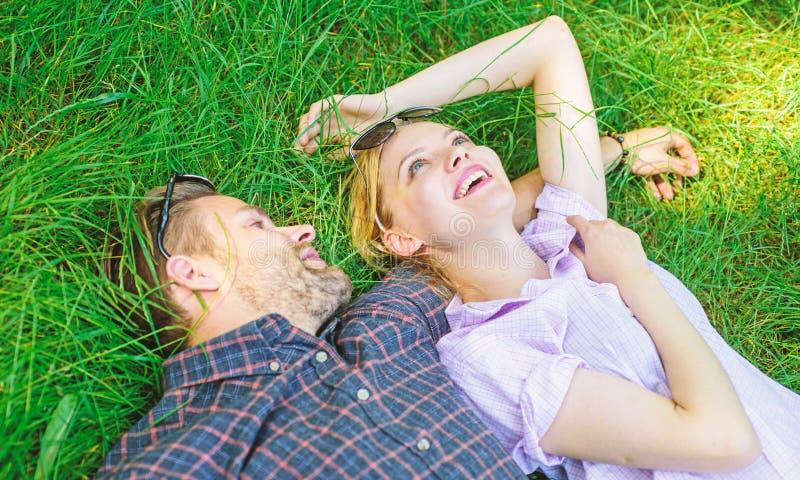 结合在爱放松的位置在草甸 自然用生气勃勃和和平填装他们 不剃须的人和女孩在草放置 免版税图库摄影
