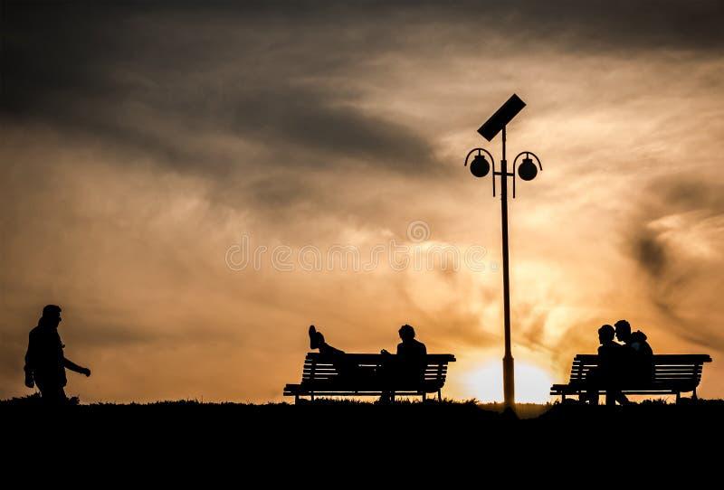 结合在爱的剪影在长凳在日落 免版税库存照片