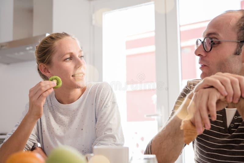 结合坐和谈话在厨房用桌上 库存图片