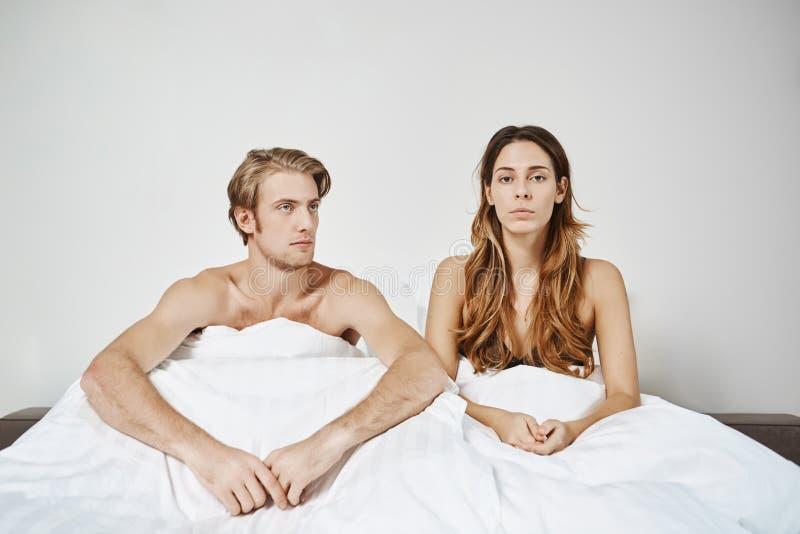 结合坐在床上在毯子下有问题在表示的卧室失望 夫妇有战斗在早晨和 库存照片
