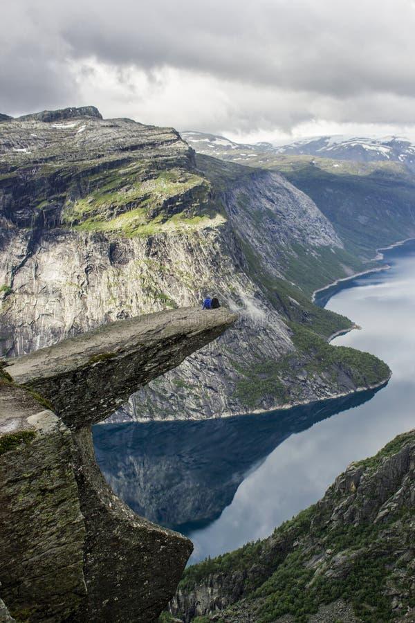 结合坐trolltunga拖钓` s舌头岩石,挪威 免版税库存图片