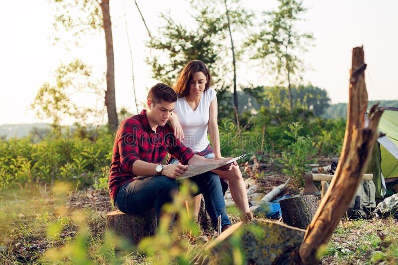 结合山的远足者,他们看地图 免版税图库摄影