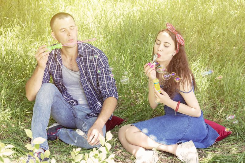 结合恋人吹泡影 朋友笑 夏天野餐男孩和女孩坐草 免版税库存图片