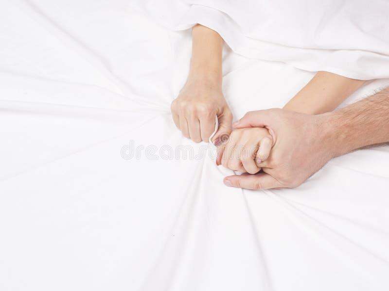 结合拉扯在销魂,性交高潮的手白色板料 激情的概念 性交高潮 色情时候 亲密的概念 性别 免版税库存图片