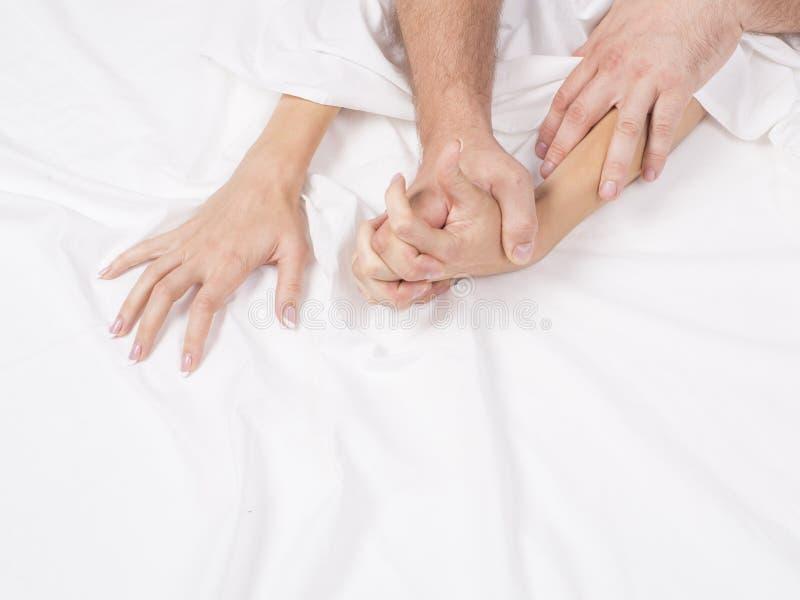 结合拉扯在销魂,性交高潮的手白色板料 激情的概念 性交高潮 色情时候 亲密的概念 性别 库存图片