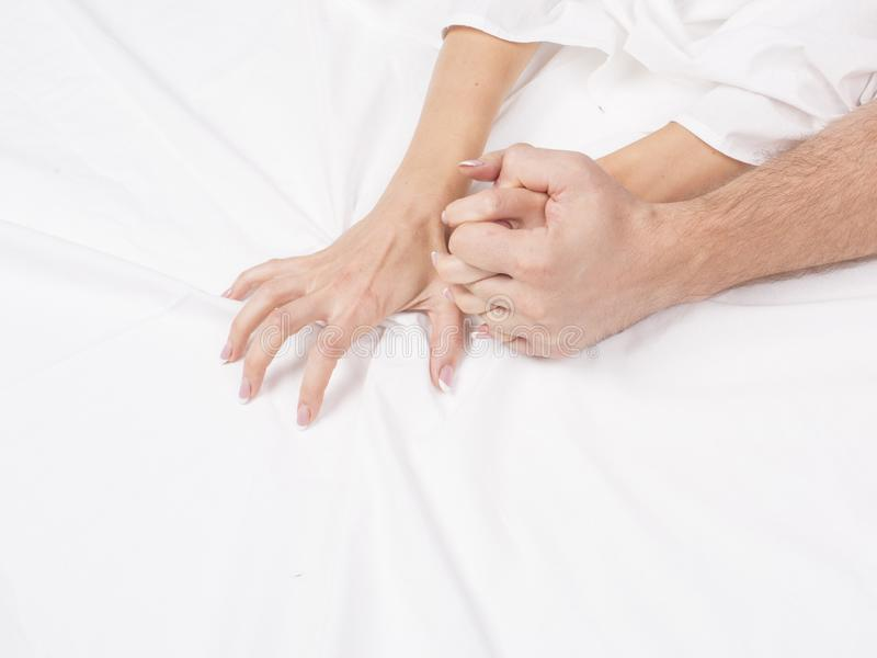 结合拉扯在销魂,性交高潮的手白色板料 激情的概念 性交高潮 色情时候 亲密的概念 性别 库存照片