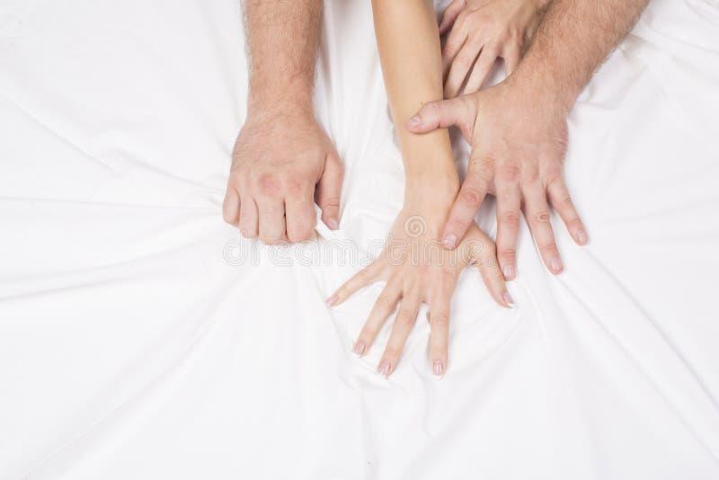 结合拉扯在销魂,性交高潮的手白色板料 激情的概念 性交高潮 色情时候 亲密的概念 性别 图库摄影