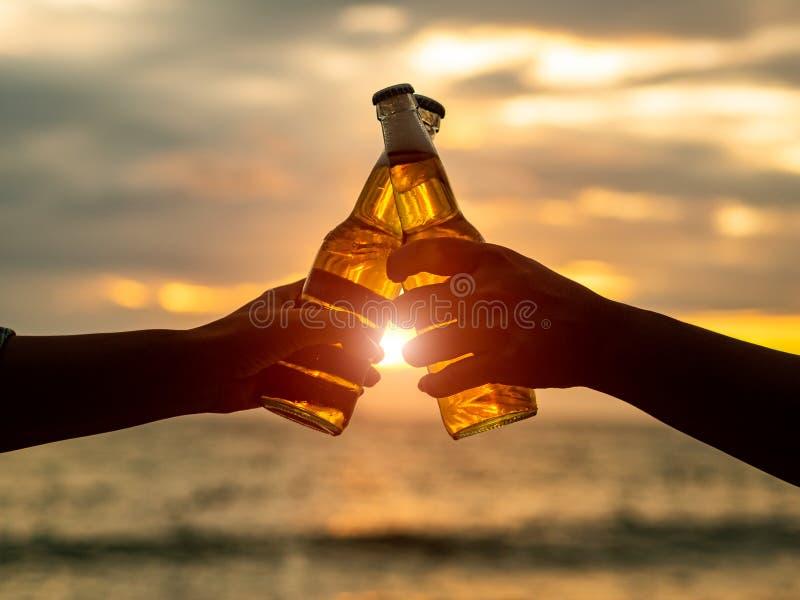 结合拿着啤酒瓶和叮当响在日落bea的手 免版税库存照片