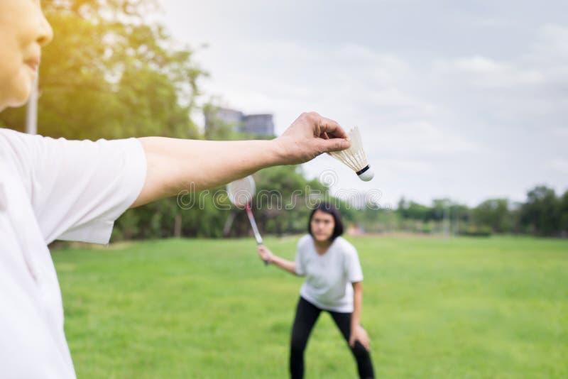 结合拿着羽毛球拍的亚洲妇女手,并且shuttlecock在公园,关闭  库存图片