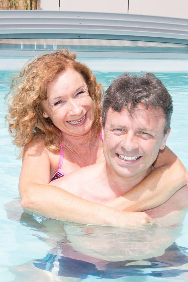 结合放松在手段在爱的游泳池 免版税库存照片