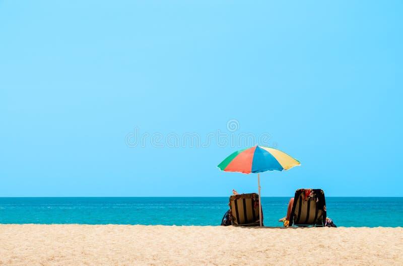 结合晒日光浴和放松在海滩睡椅 沙子和海视图,夏天背景 库存照片