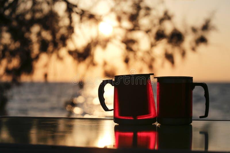 结合有日落的热水瓶杯子 免版税库存照片