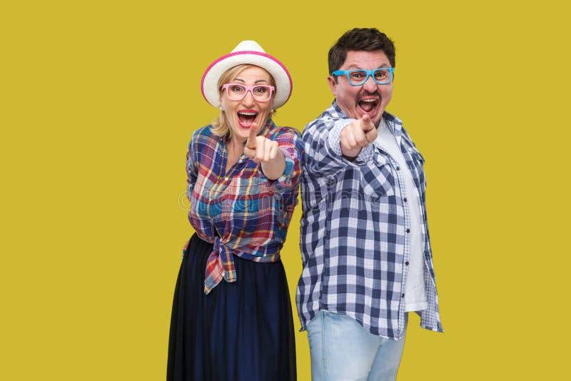结合朋友、成人男人和妇女站立偶然方格的衬衣的紧接一起指向手指,看起来惊奇, 库存图片