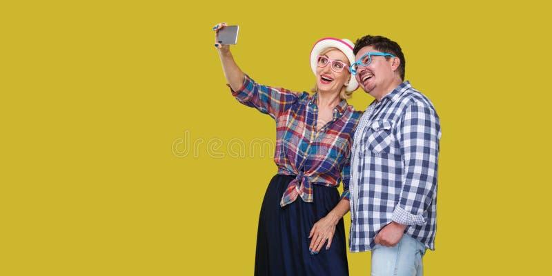 结合朋友、逗人喜爱的成人男人和妇女一起站立和做selfie foto记忆或录影的偶然方格的衬衣的 免版税库存图片