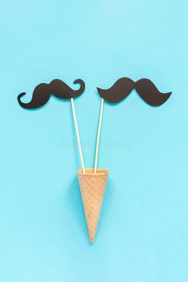 结合纸在棍子的髭支柱在冰淇淋在蓝色背景的奶蛋烘饼锥体 概念同性恋快乐爱 国际 免版税库存照片