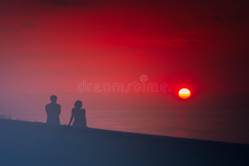 结合观看的美好的红色日落 免版税库存图片