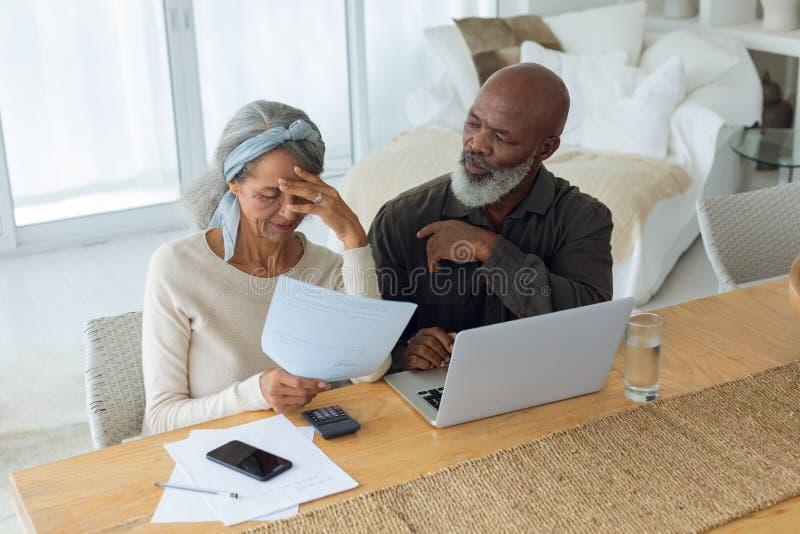结合谈论纸和使用在屋子里面的膝上型计算机 免版税库存照片