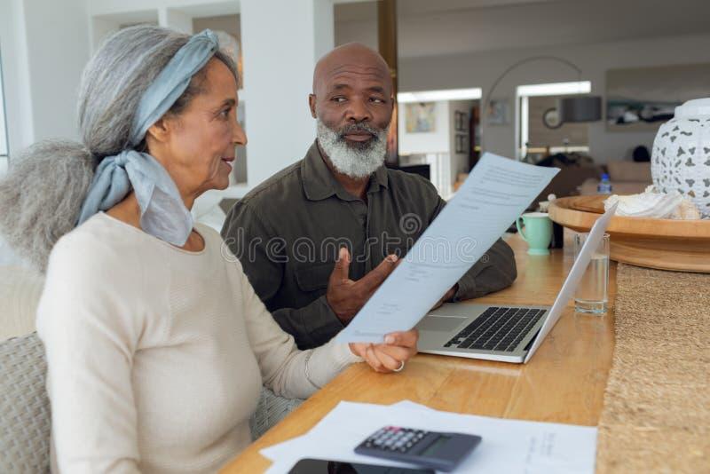 结合谈论纸和使用在屋子里面的膝上型计算机 免版税库存图片