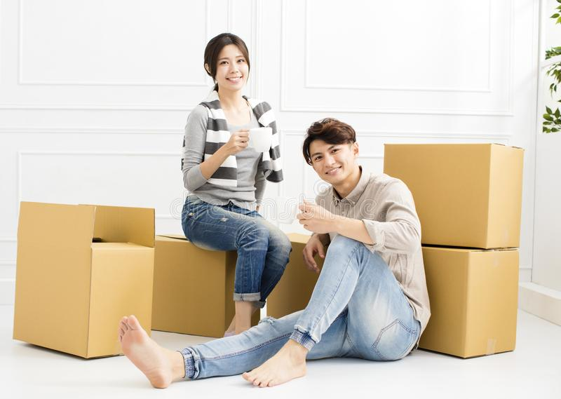 结合运载的箱子入新的家和饮用的咖啡 免版税库存图片