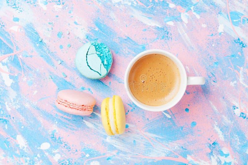 结块macaron或蛋白杏仁饼干和咖啡在五颜六色的台式视图 平的位置 创造性的早餐为妇女天 有魄力的柔和的淡色彩 免版税库存照片