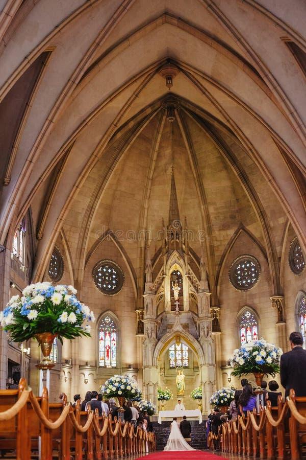 结婚在一个美丽的哥特式教会里的夫妇 免版税图库摄影