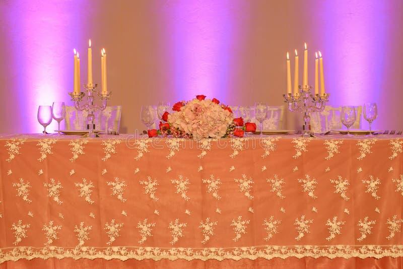 结婚宴会或美好的饭桌设定与被绣的透明硬沙桌布、水晶蜡烛台和植物布置 免版税库存图片