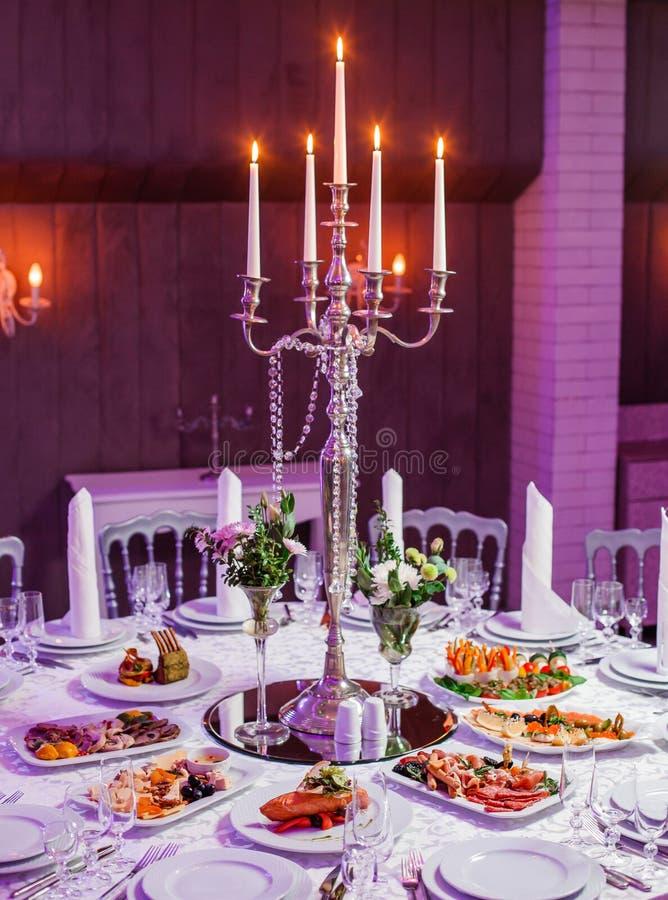 结婚宴会晚餐 圆桌服务与花、发光的蜡烛和开胃菜食物 假日宴会菜单 免版税库存照片