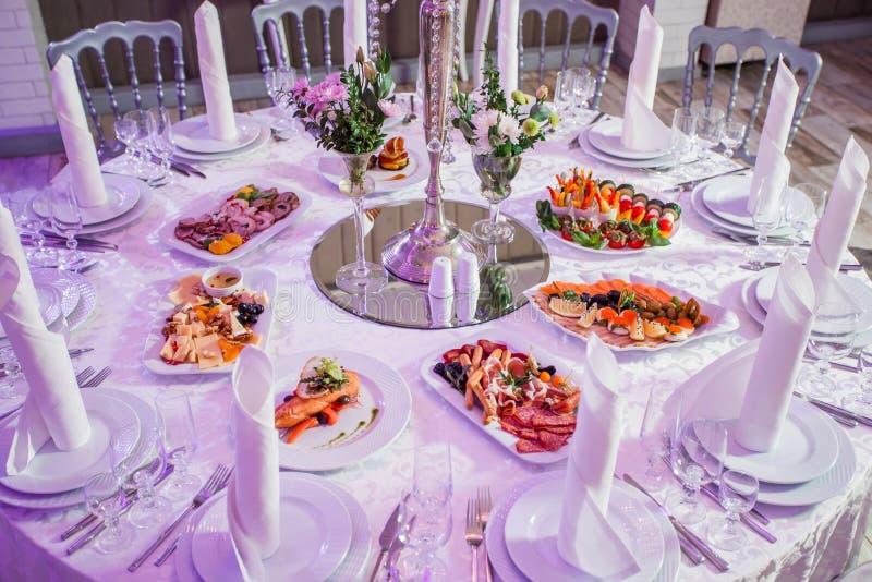 结婚宴会晚餐 圆桌服务与花、发光的蜡烛和开胃菜食物 假日宴会菜单 免版税库存图片