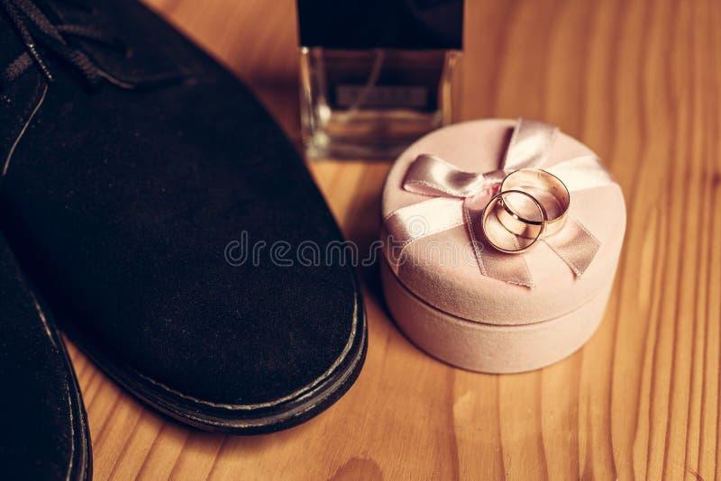 结婚戒指和鞋子-新郎的婚姻的细节 免版税库存照片