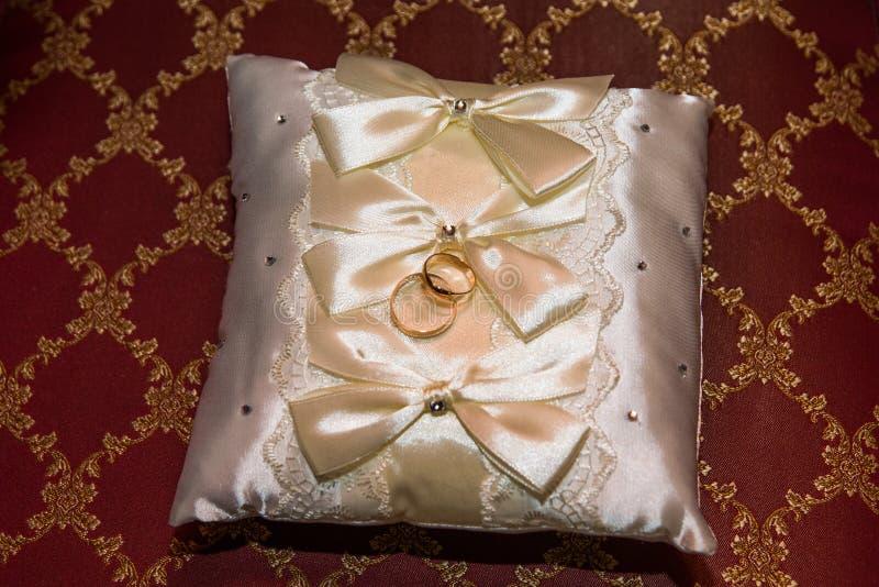 结婚戒指在一个白色枕头和sadely新娘的花束 免版税库存照片