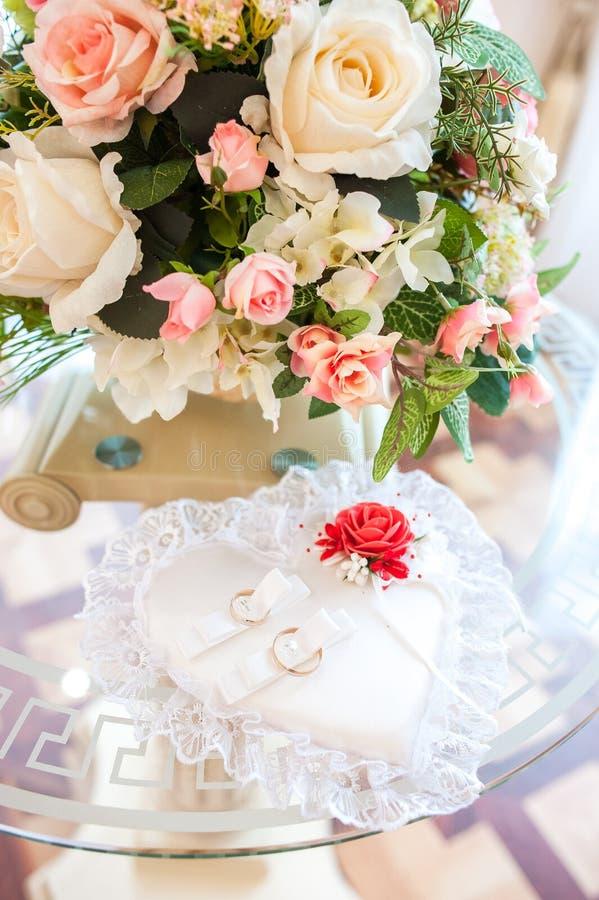 结婚戒指在一个美丽的心形的枕头说谎 婚姻的装饰 图库摄影