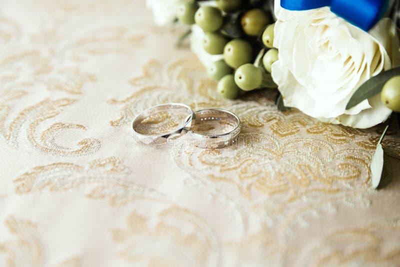 结婚戒指在织品说谎在一束花旁边 免版税库存图片